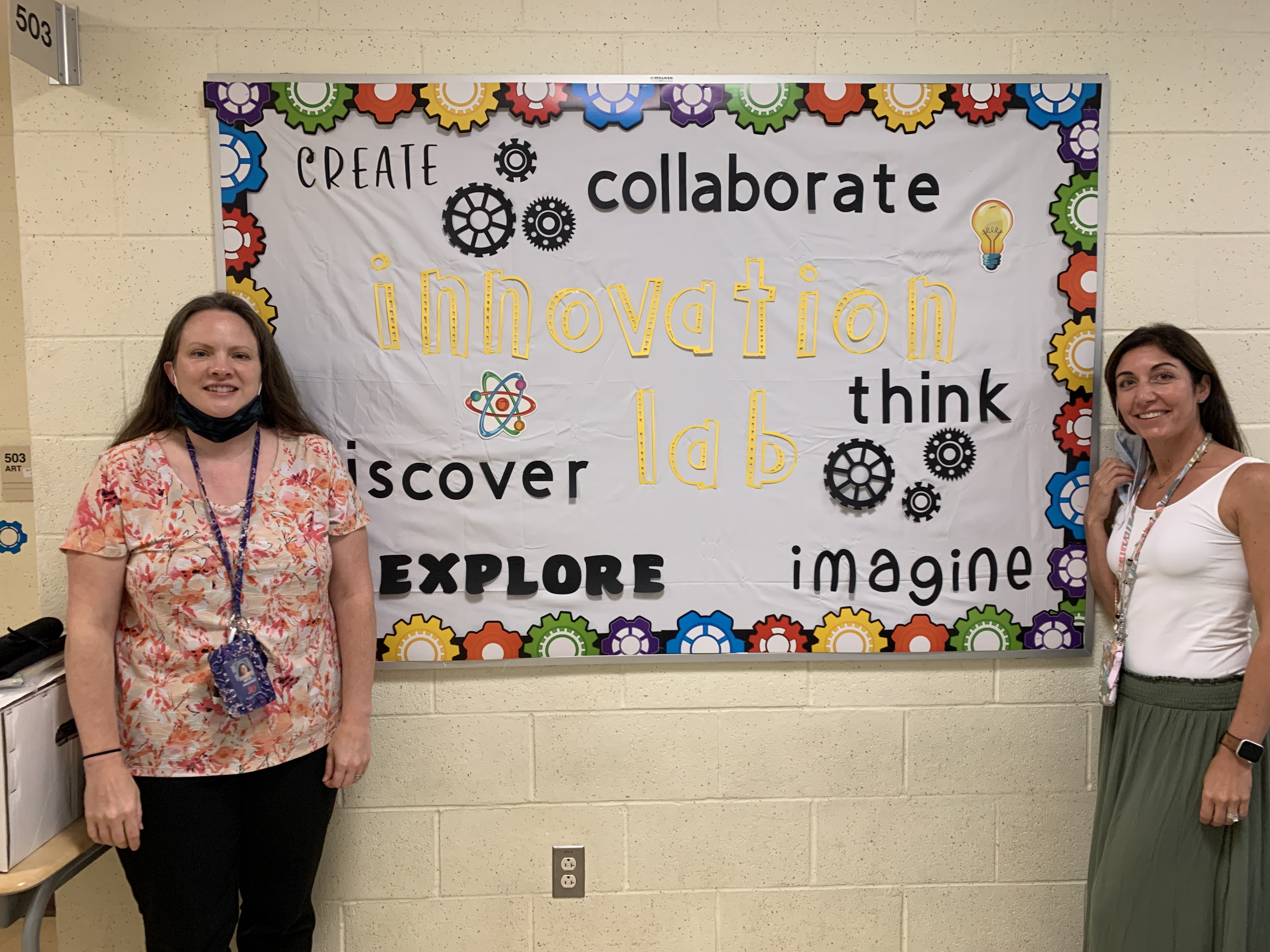 Teachers in front of the Innovation Lab bulletin board