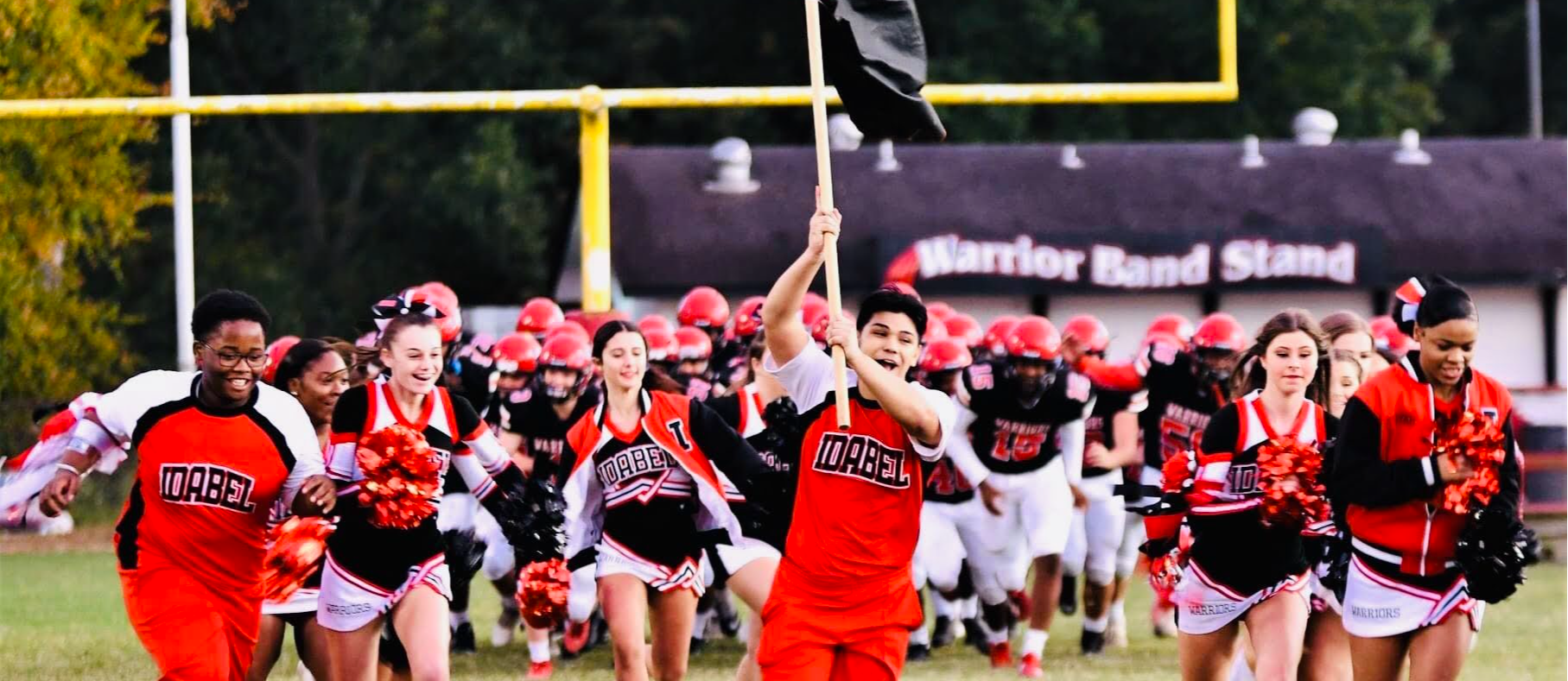 Student running with flag before football game
