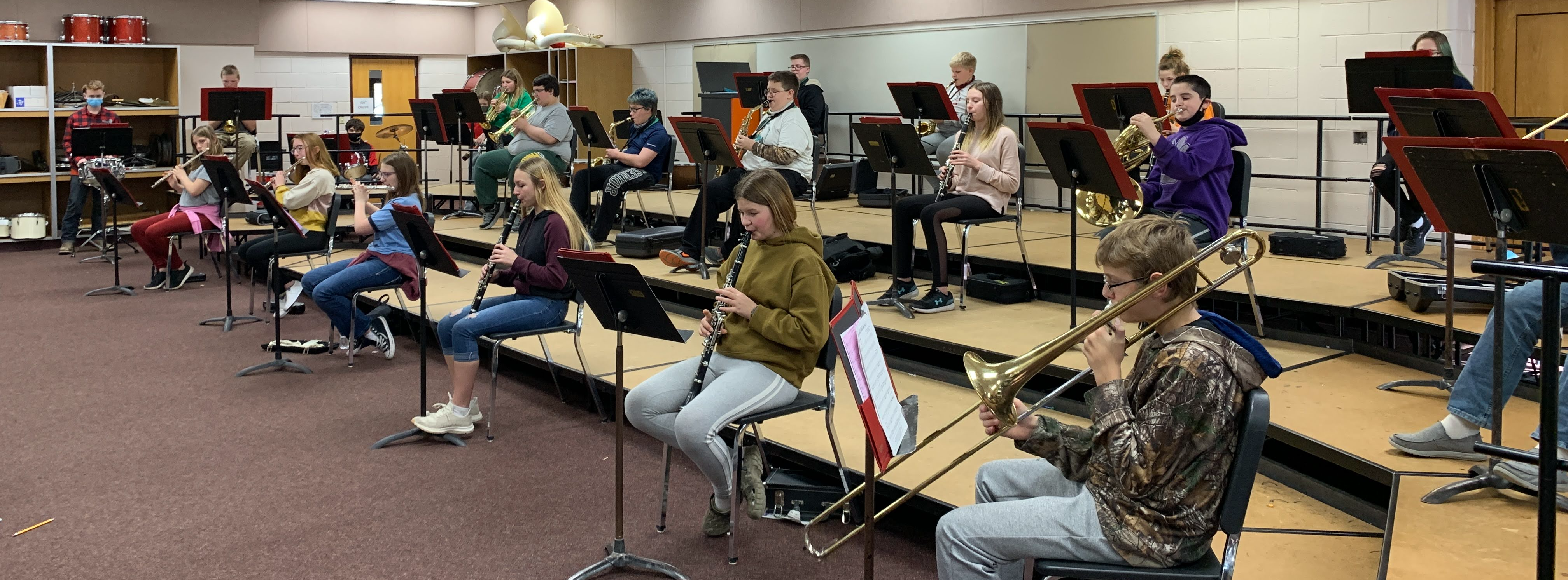 Band students playing instruments in classroom